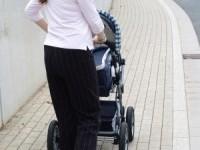 Moeder die een kinderwagen duwt